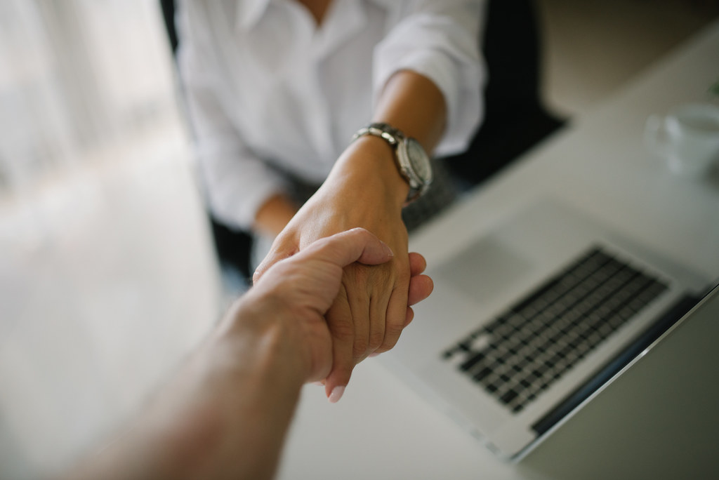 This is an image of a firm handshake across a desk, the typical ending to a well done job interview.