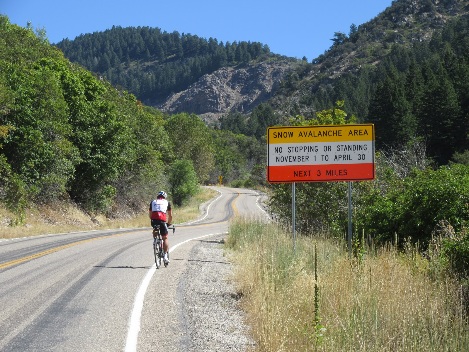 Cyclist passing avalanche warning roadway sign on Powder Mountain top US bike climb