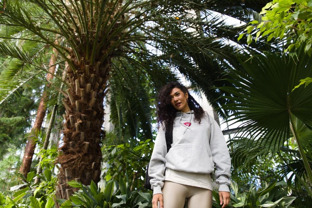 woman in a jungle in a hoodie