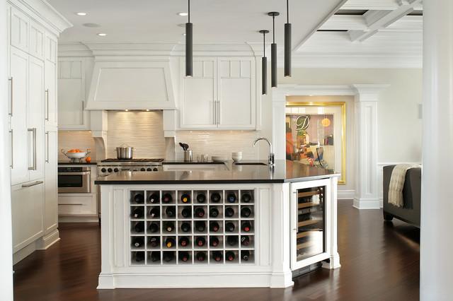 large traditional white kitchen with black countertops, custom island with wine rack and wine fridge, paneled fridge and white shaker cabinets with chrome hardware