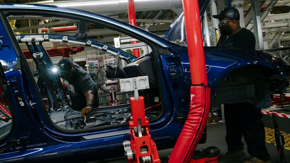 FREMONT, CA - JULY 26: Damien Boozer and Paul Jacob work on the general assembly of the Tesla Model 3 at the Tesla factory in Fremont, California, on Thursday, July 26, 2018. (