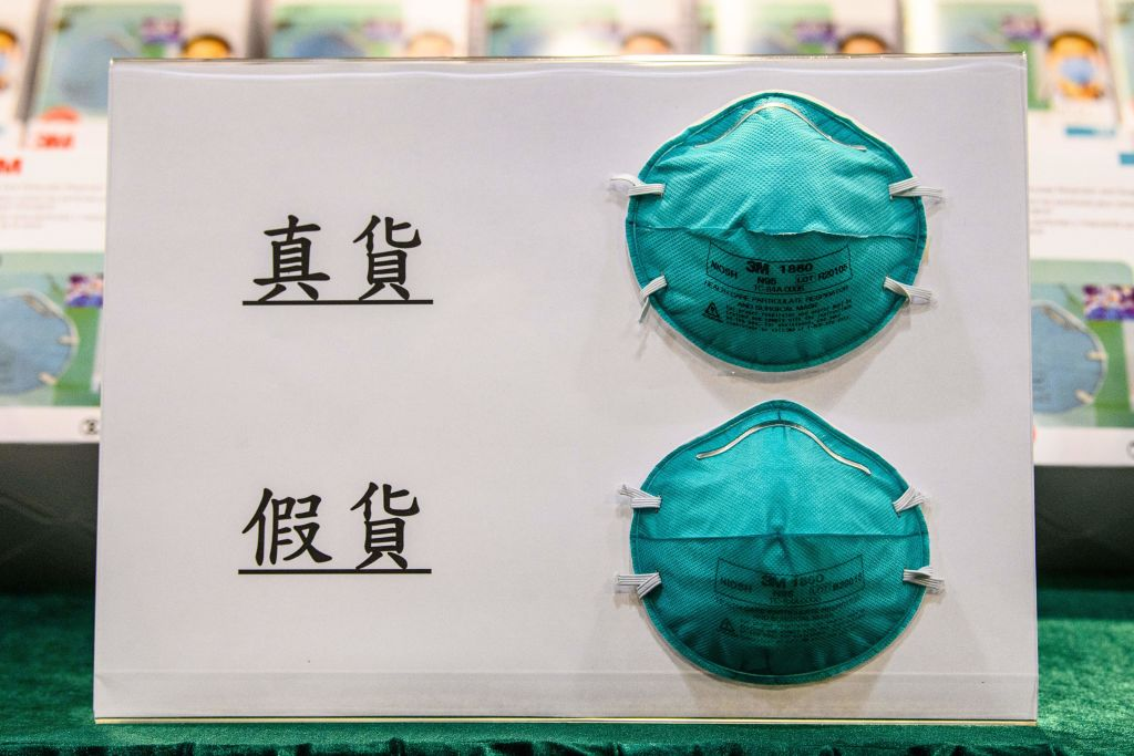 Examples of a real (top) and fake (bottom) mask are shown on a display board during a press conference at the Customs Headquarters Building in Hong Kong on October 30, 2020. Fake 3M masks were seized in addition to counterfeit vaccines by South African police