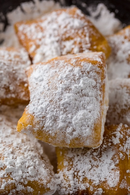 A pile of New Orleans-style beignets dusted with powdered sugar