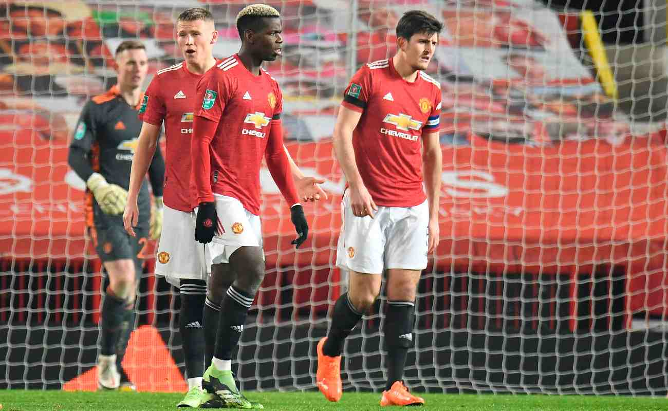 Alt: Paul Pogba, Scott Mctominay, and Harry Maguire react after a goal is scored against Manchester United - Photo by PETER POWELL/POOL/AFP via Getty Images