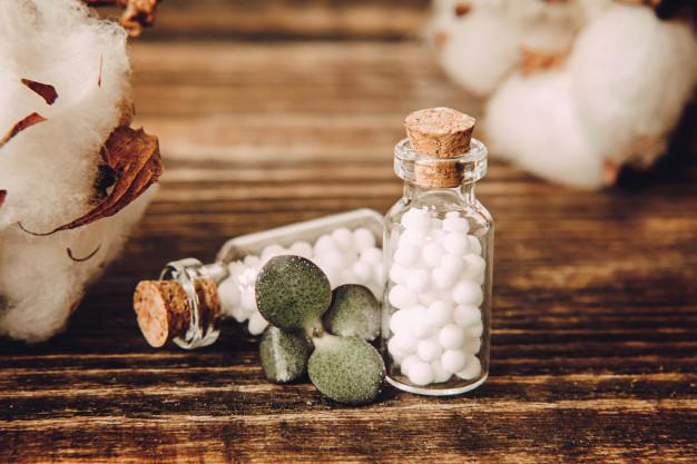 Homeopathic globules and glass bottle close up on wooden surface. Premium Photo