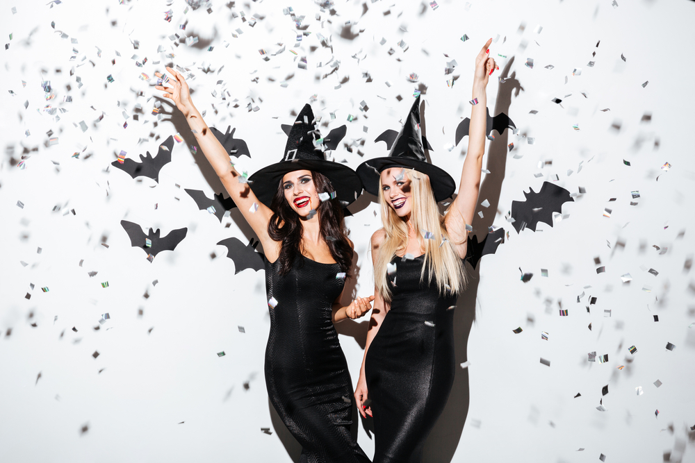 two women in glamourous witch costumes for Halloween