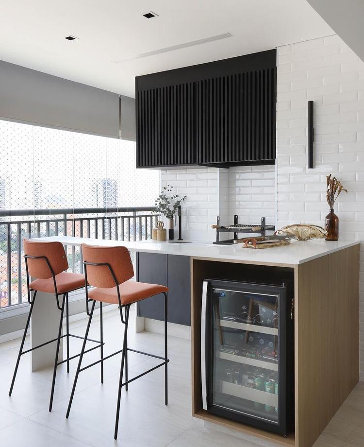 Área gourmet com subway tiles branco nas paredes, bancada d emadeira branca com armário amadeirado, cadeiras laranja e piso porcelanato branco.