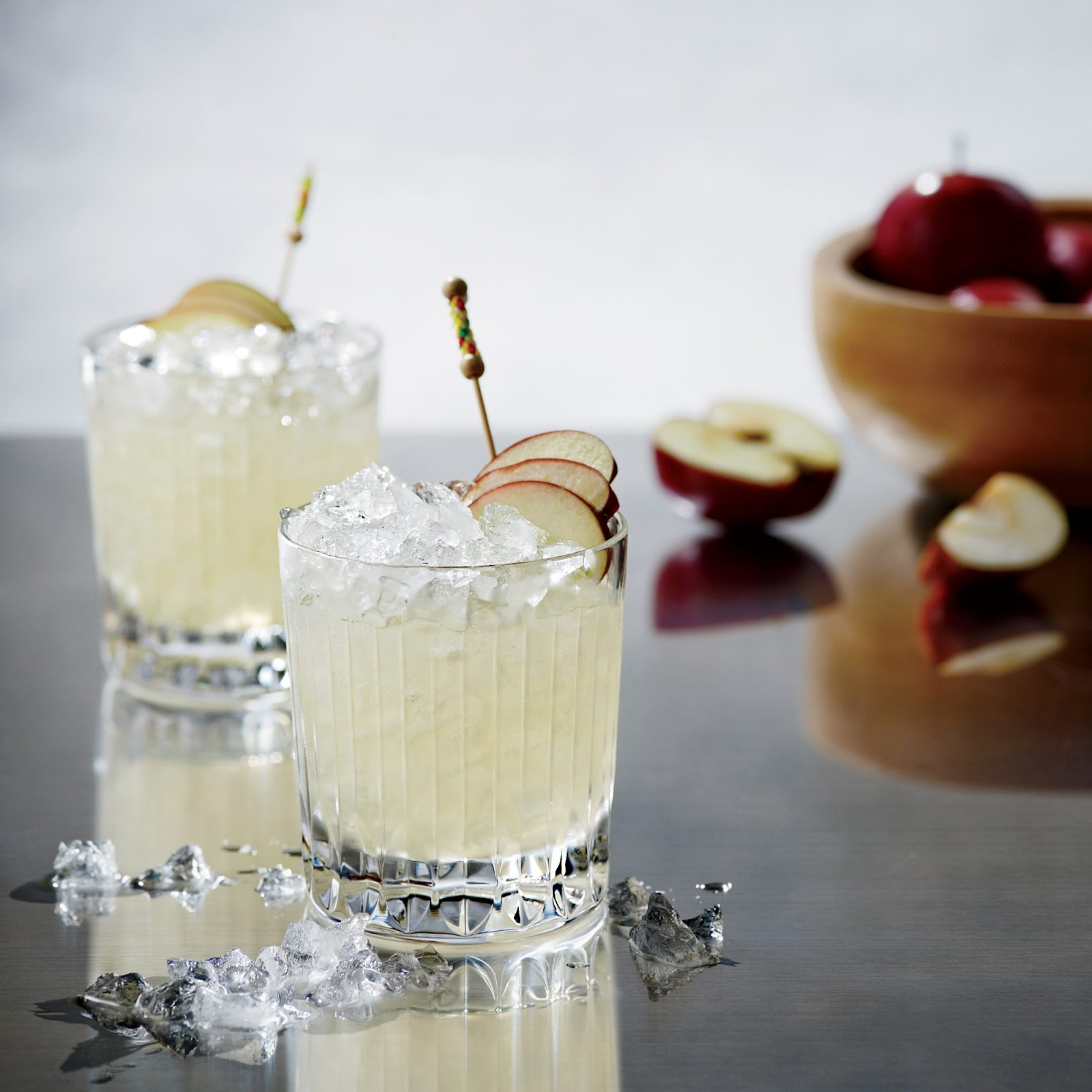 2 Orchard Mai Thai mocktails in rocks glasses with crushed ice & apple garnishes with bowl of apples in background