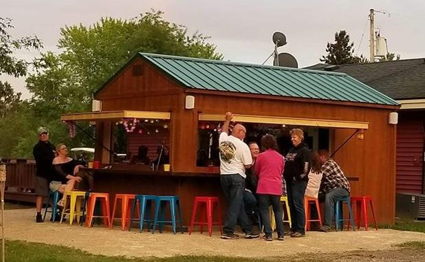 Outdoor tiki bar at campground with colorful chairs and people talking