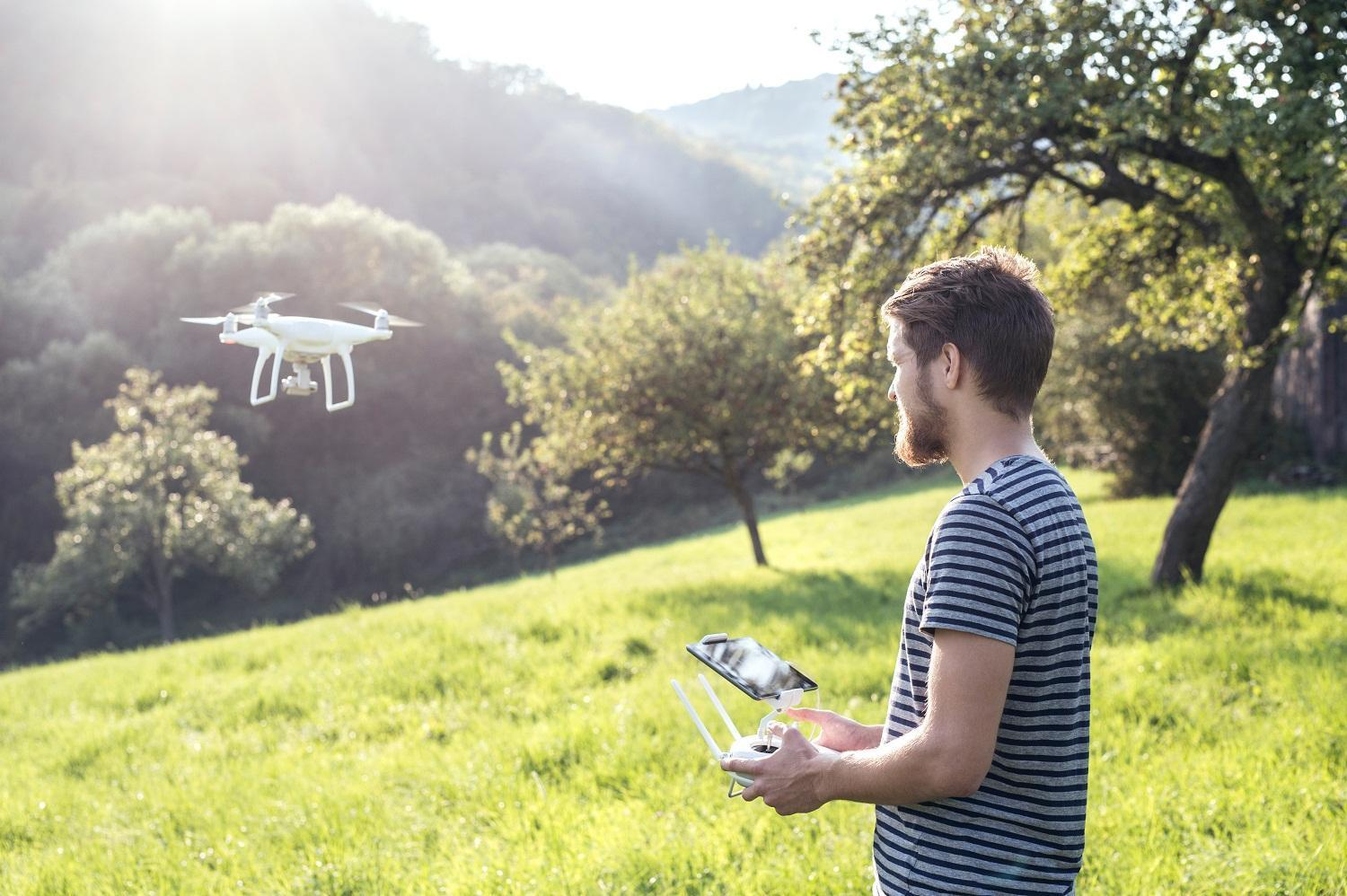man-with-remote-control-and-flying-drone-with-camera.jpg