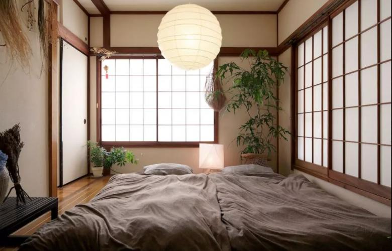2 grey floor beds with plants at the corners of the room, and a circle pendant light