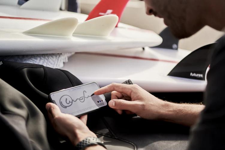 A imagem mostra um homem assinado um documento de compra e venda de imóvel pelo celular com a mão direita. A assinatura é feita na tela, em touch-screen.