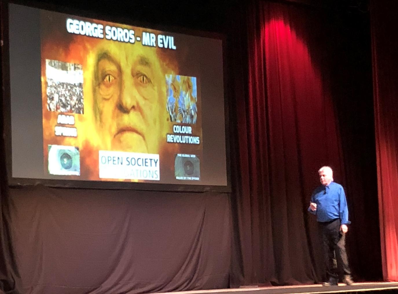 """A photo taken at the 2018 David Icke tour. David Icke stands on a stage in Southport wearing a blue shirt, black trousers and a pair of brown boots. The screen at the back of the stage shows a photo of George Soros mocked up as the centre of a burning eye, his eyes are edited to look like lizard's eyes and his face has been coloured yellow. The heading says """"George Soros - Mr Evil"""""""
