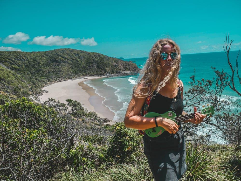 Woman Standing on Mountain While Playing Guitar Near Seashore