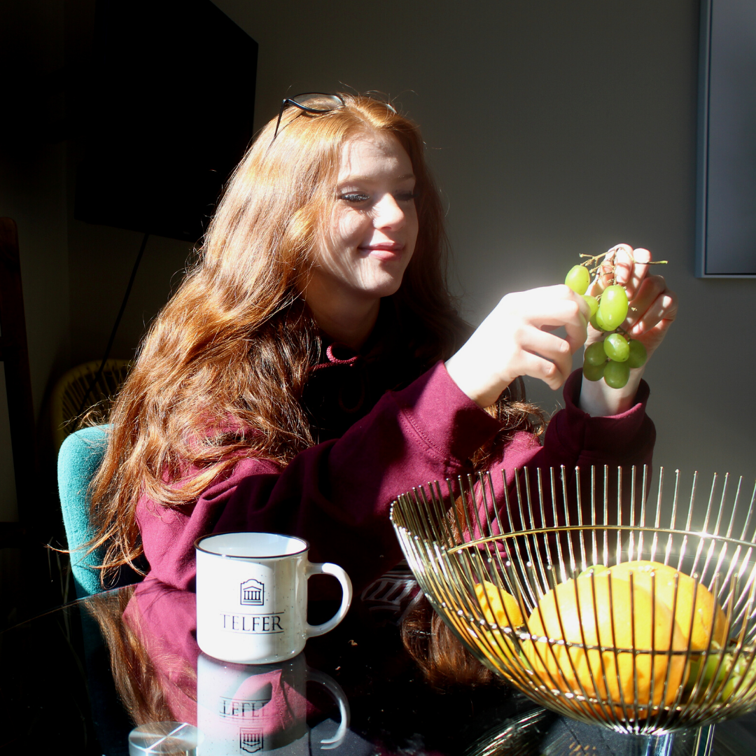 Young woman eating grapes at a table