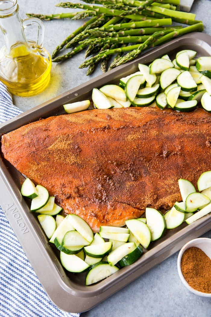 A sheet pan with an uncooked fillet of coho salmon