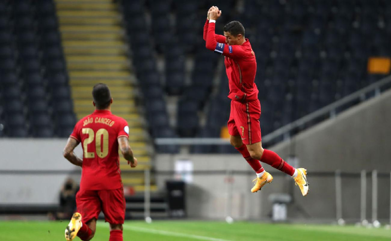 Alt: Cristiano Ronaldo jumps in the air and celebrates scoring a goal for Portugal - Photo by Linnea Rheborg/Getty Images