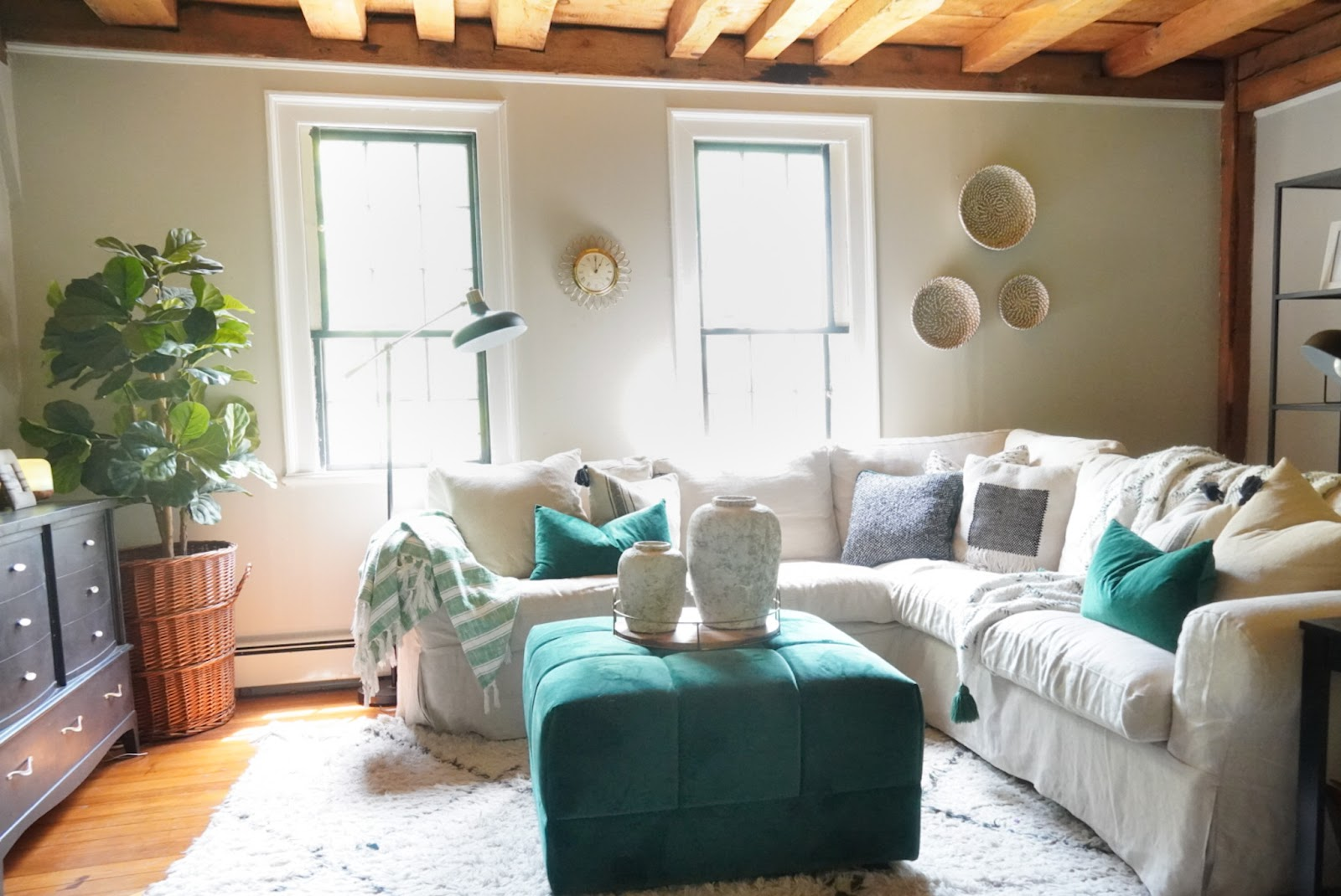 Living room with a white slipcover couch, green ottoman, and white a green throw pillows.
