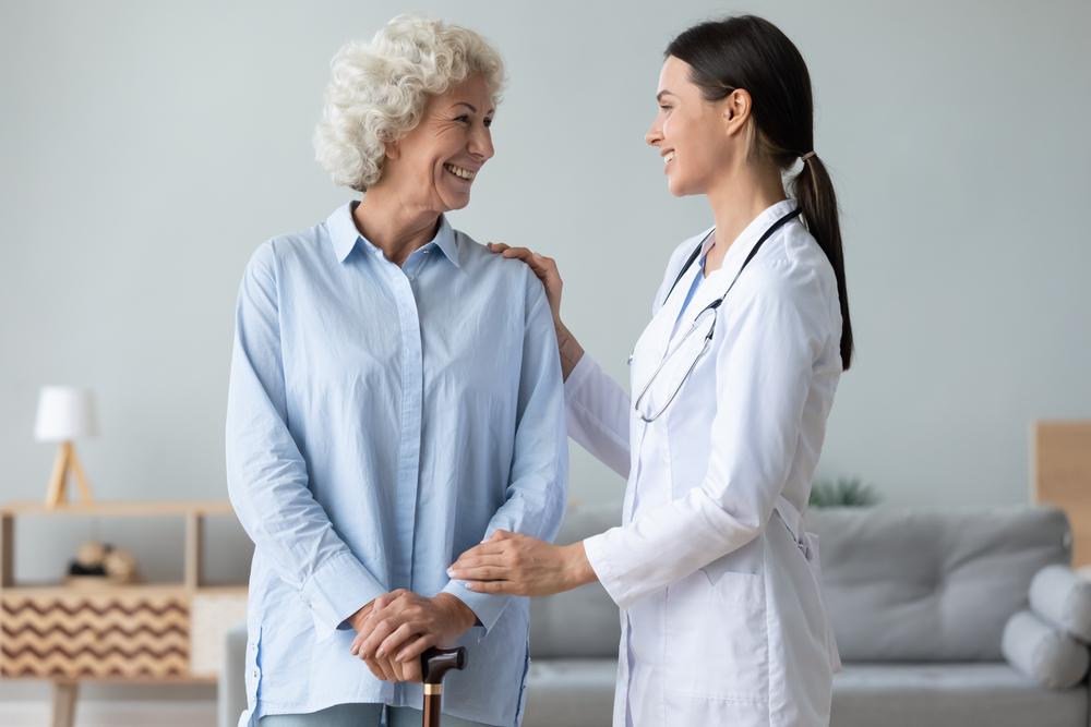 Médica tocando ombro e mão da paciente senhora em tom de incentivo