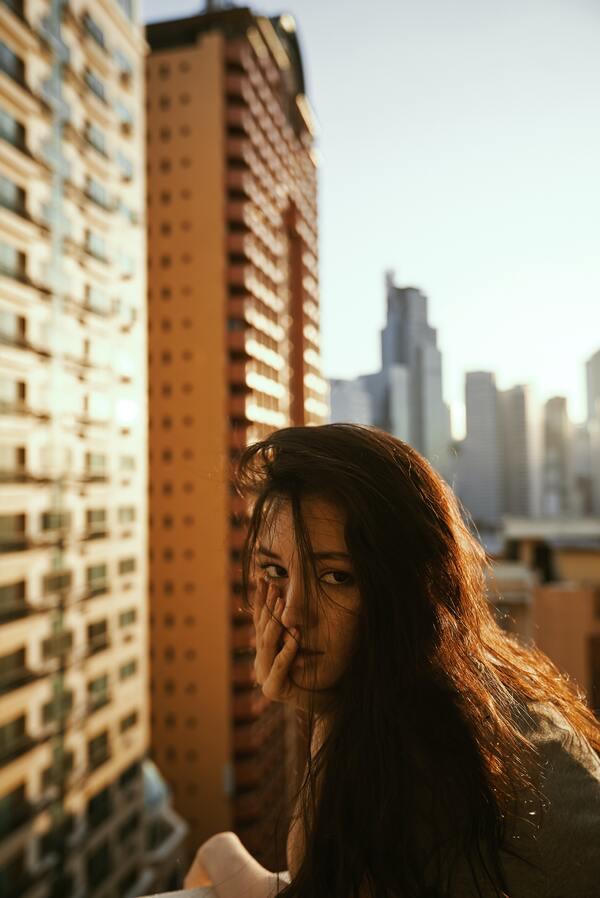Foto de uma menina em uma sacada, com prédios ao fundo.