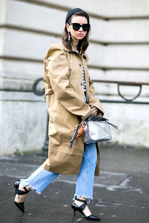 Le Fashion Blog Fall Street Style Natasha Goldenberg Oversized Sunglasses Drop Earrings Long Camel Trench Coat Striped Top Deconstructed Metallic Silver Loewe Bag Raw Hem Jeans Short Strappy Pumps Via Popsugar