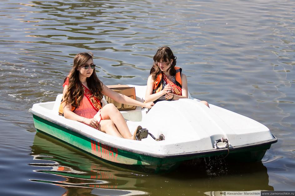 Выпускницы катаются на лодочке в водоёме