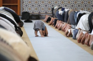 A child is seen near members of the Muslim community attending midday prayers at Strasbourg Grand Mosque in Strasbourg on the first day of Ramadan July 9, 2013. The Grand Mosque of Paris has fixed the first day of Ramadan as Wednesday, splitting with the French Council of Muslim Religion (Conseil Francais du Culte Musulman or CFCM), which determined it would begin on Tuesday.  REUTERS/Vincent Kessler