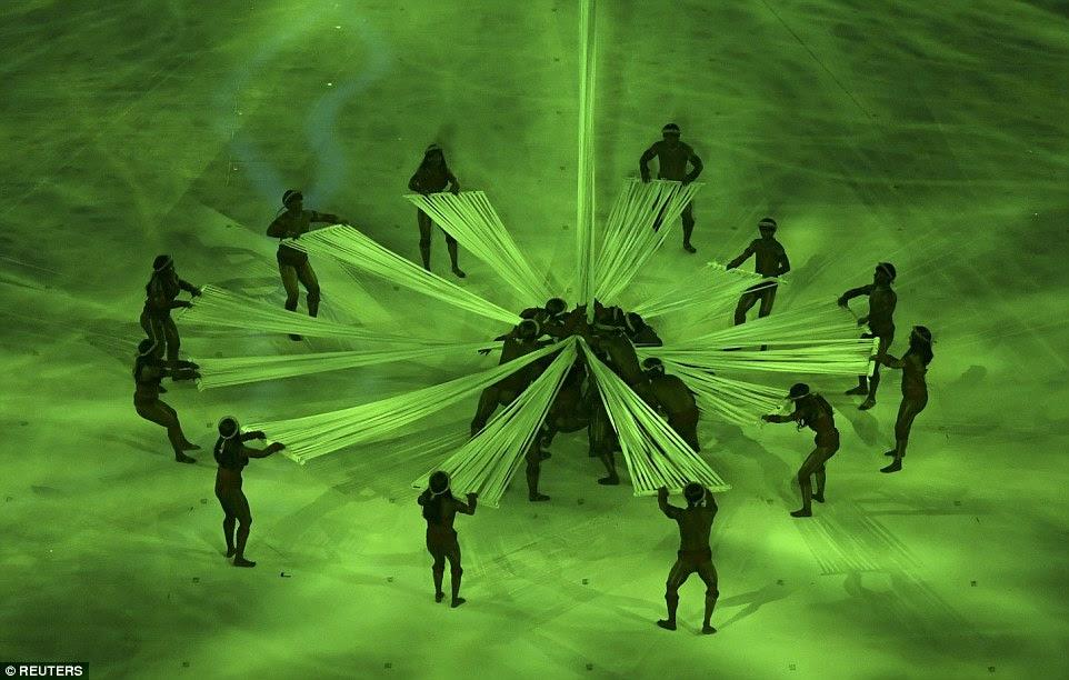 Iluminado em verde, os dançarinos representaram as centenas de tribos que populares da floresta amazônica no Brasil
