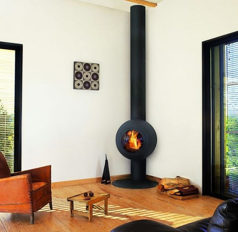 unique and small modern wood burning stove in black some wood logs an arm chair with small and low wood table brushed wood flooring