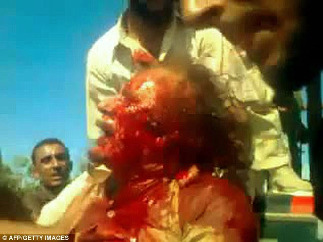 Grimacing in pain: A still from a video taken from the mobile phone of a rebel fighter shows Gaddafi, his face covered in blood, being dragged around by freedom fighters