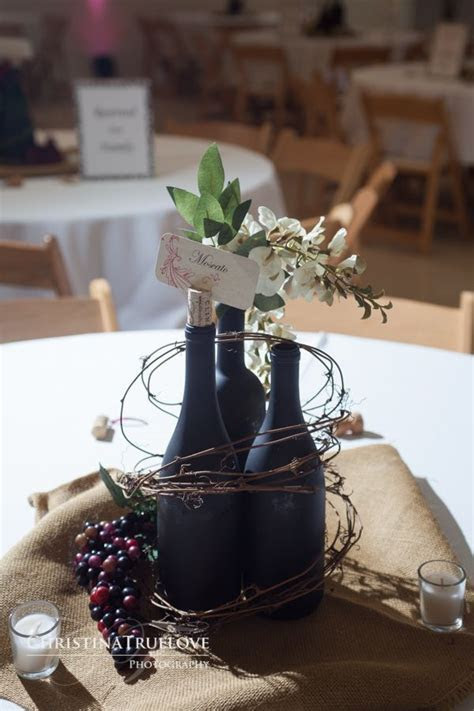 Love this wine bottles, grapes and twig centerpiece idea