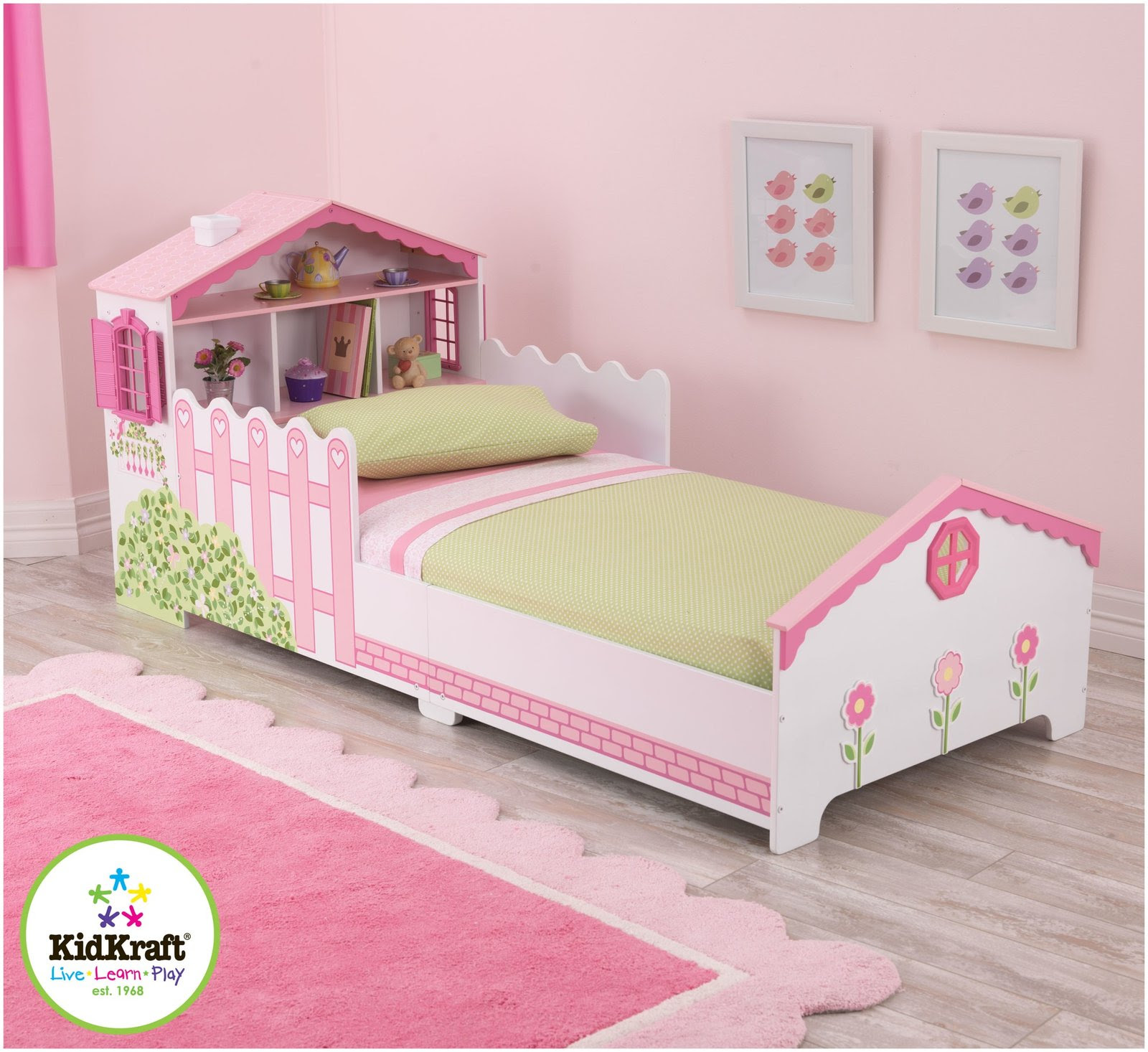 Dollhouse toddler bed by kidkraft with wood construction and painted finishing and bookshelf headboard surrounded with pink color