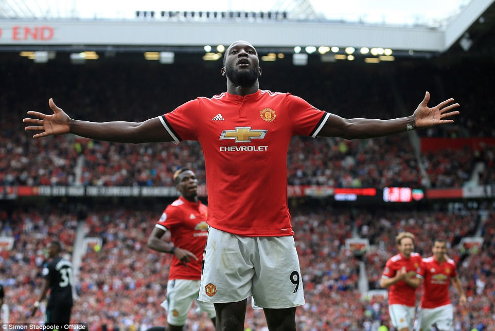 Romelu Lukaku raises his arms aloft in front of the Old Trafford stands as Paul Pogba runs to celebrate with his new team-mate