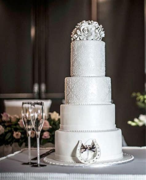 4 tier elegant round wedding cake with horseshoe at base