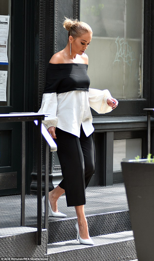 Daring to be different: Rita sported a black bardot top fused with a white, menswear style shirt with bouffant sleeves
