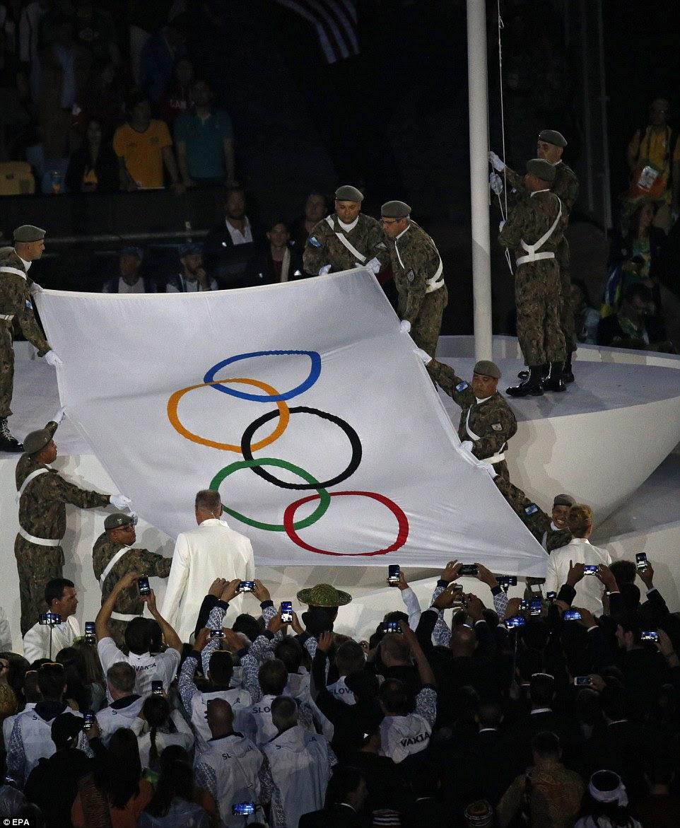 A bandeira olímpica foi levada para o palco no estádio e levantada por membros das forças armadas