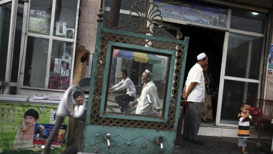 Members of the Uighur community walk past a restaurant in Xinjiang province.