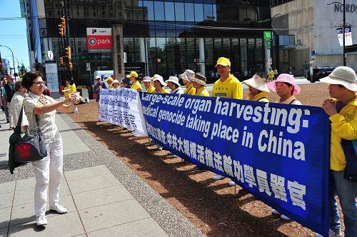 """图3-5:七月二十日,法轮功学员在市中心举行纪念""""七二零""""活动,揭露中共活摘法轮功学员器官的罪恶,呼吁制止迫害。吸引行人观看和了解真相。"""
