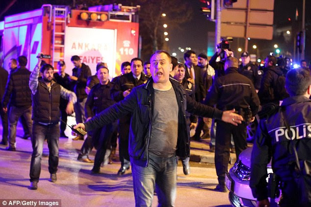 Chaos: A man reacts next to policemen near the site of an explosion after an attack targeted a convoy of military service vehicles in Ankara