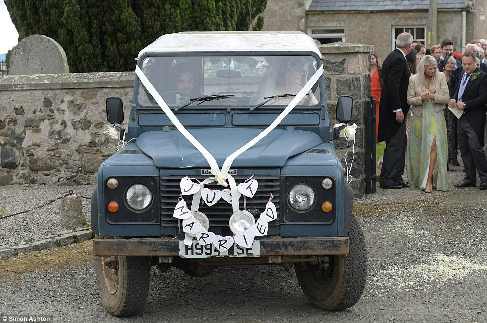Arriving in style: Later on, Kit helped his blushing bride into a rusty blue H-reg Land Rover Defender, which had the words 'Just Married' stuck to the radiator and tin cans tied to the back