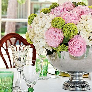 Dress Up a Summer Table w fresh flowers    Showcase the bounty of the season with a lush arrangement of pink peonies, white hydrangeas, and green viburnums. Presenting them in a silver punch bowl lends just the right level of refinement to the table.