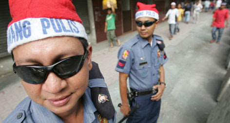 Philippine policemen wearing Santa hats are deployed in downtown Manila on Monday. The program aims to bring police closer to the public as increased visibility along high traffic areas will be implemented during the holiday season, officials said.