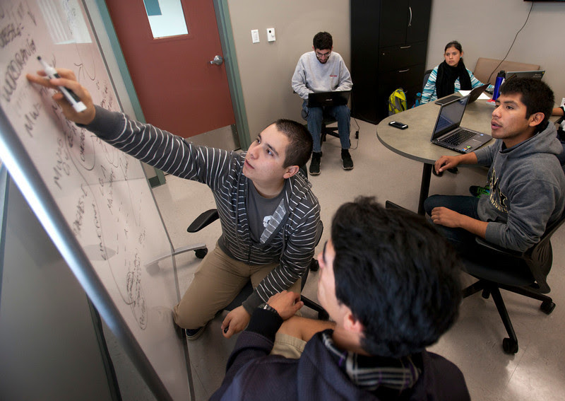 Brian De Anda helps to write programming code as his fellow students look on at the Hartnell College Alisal Campus in Salinas Friday, Oct. 25, 2013.  From left are, De Anda, Daniel Diaz, Thang Fenton, Monse Hernandez and Mateo Sixtos. The college has a unique program that aims to get rural, low-income, minority students into the computer sciences in an amazingly short time. It is CSIT-In-3--short for  Computer Science And Information Technology Bachelor's Degree in 3 Years.  (Patrick Tehan/Bay Area News Group)
