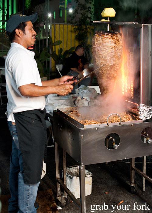 al pastor spit roast pork at el flamin taco truck in little korea, los angeles