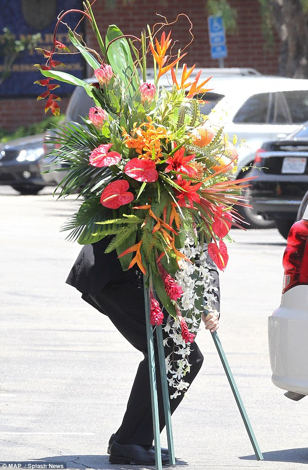 Arrangements: Large flowers were seen carried out of the church following the service