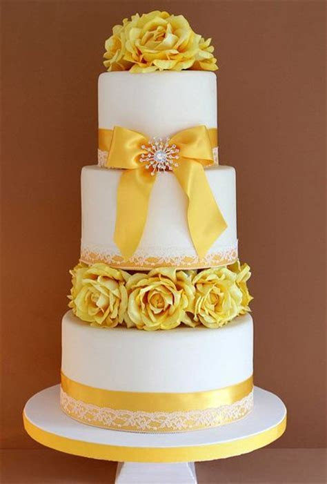 Three tier round white wedding cake with yellow flowers