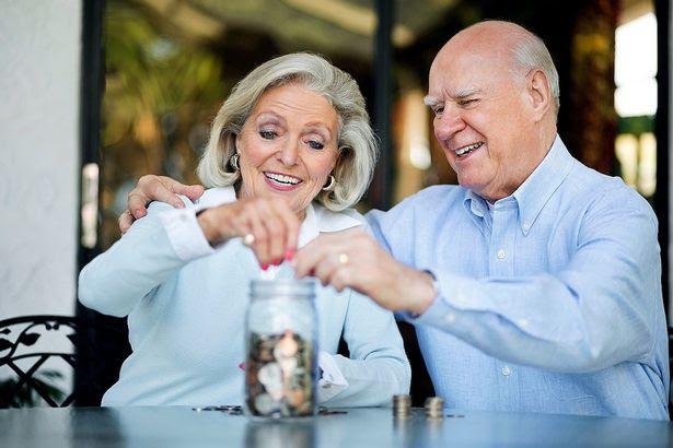 Senior Couple Saving Money In Jar