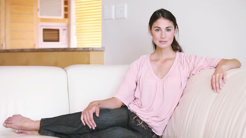 Pretty Woman Sitting On Sofa In Bright Living Room, Having Tea ...