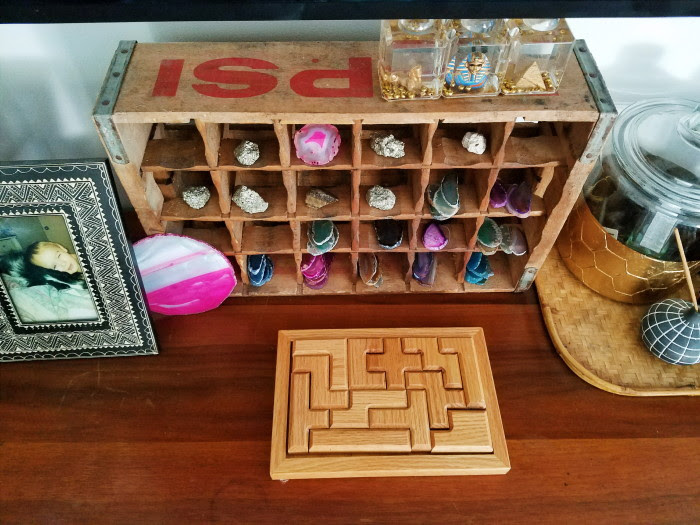 Soda crate with rock and agate collection and a wooden puzzle