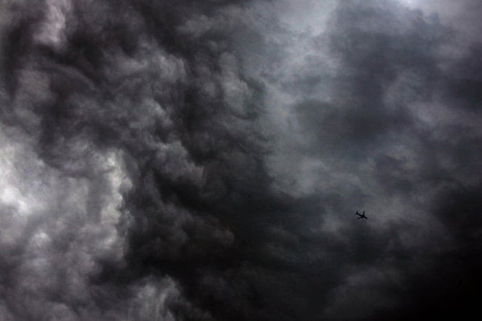 A Qantas Airways Boeing 737-800 flies through storm clouds above Sydney after the Australian Bureau of Meteorology issued a severe thunderstorm warning